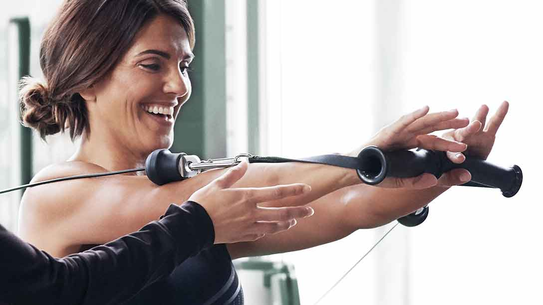 A smiling woman uses the dual cable cross machine with guidance from a trainer